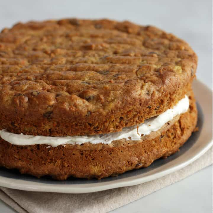 round, two-layer carrot cake with frosting filling between the layers