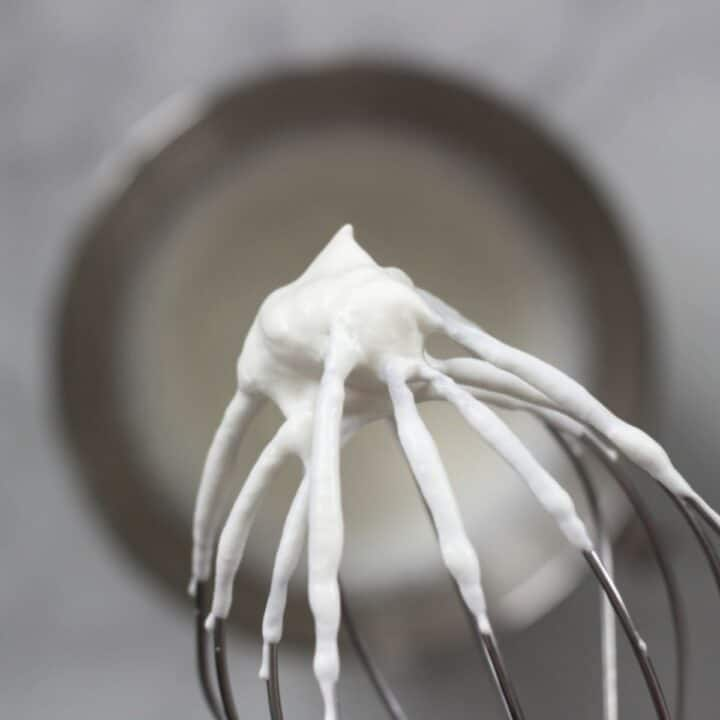 closeup of stiffly beaten whipped cream on whisk held over bowl