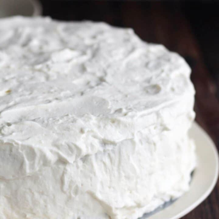 close up of white frosting on round cake