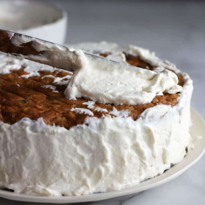 fluffy white frosting being spread over round layer cake