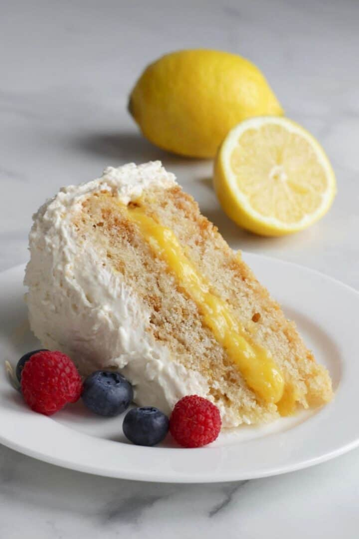 closeup of lemon cake wedge on white plate with berries to the side