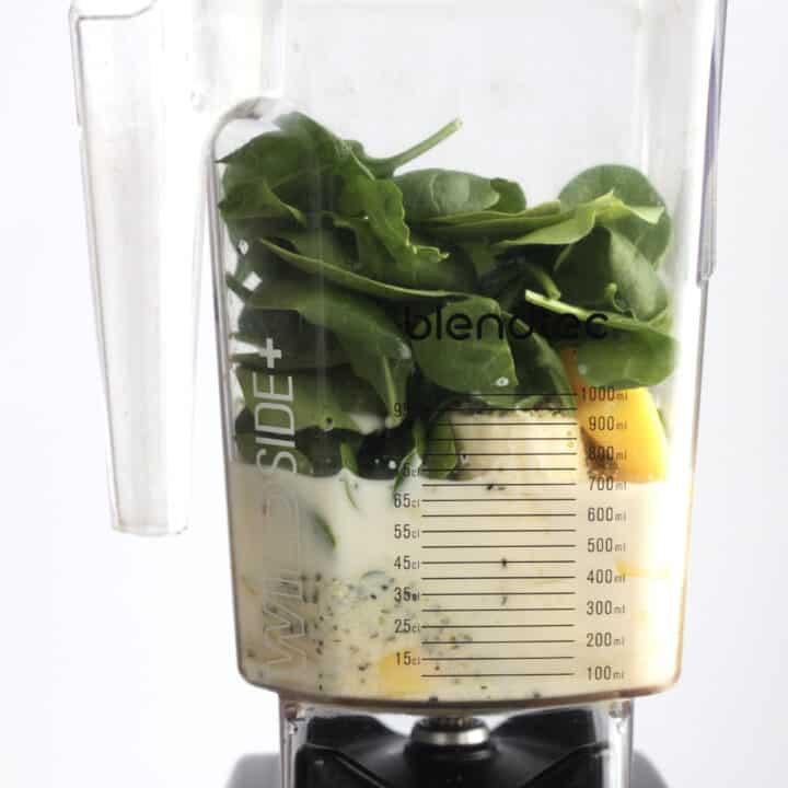 spinach, mango, banana, and almond milk in blender jar