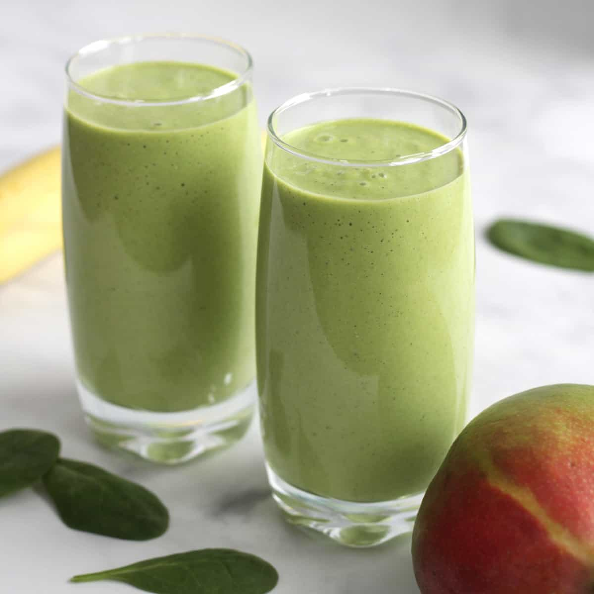 two glasses of green smoothies and partial mango, banana, and spinach leaves around them