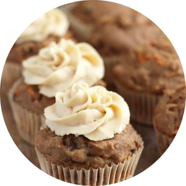 carrot cake muffins with swirls of frosting on top