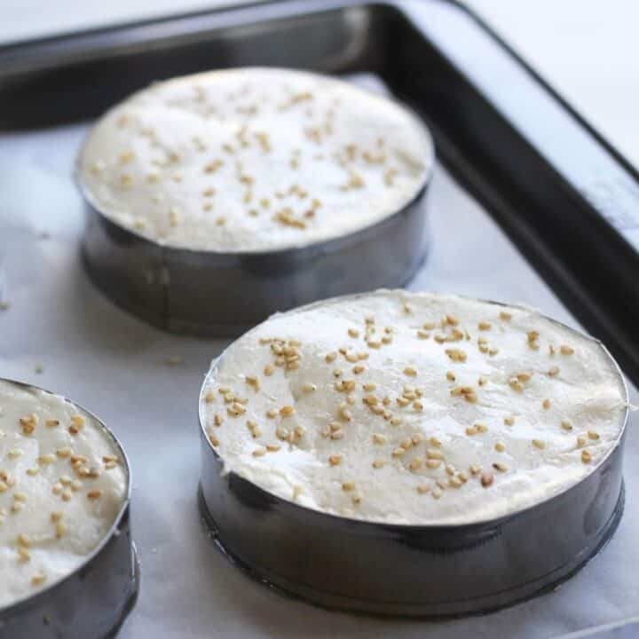 batter sprinkled with sesame seeds fills metal rings on parchment-lined baking sheet
