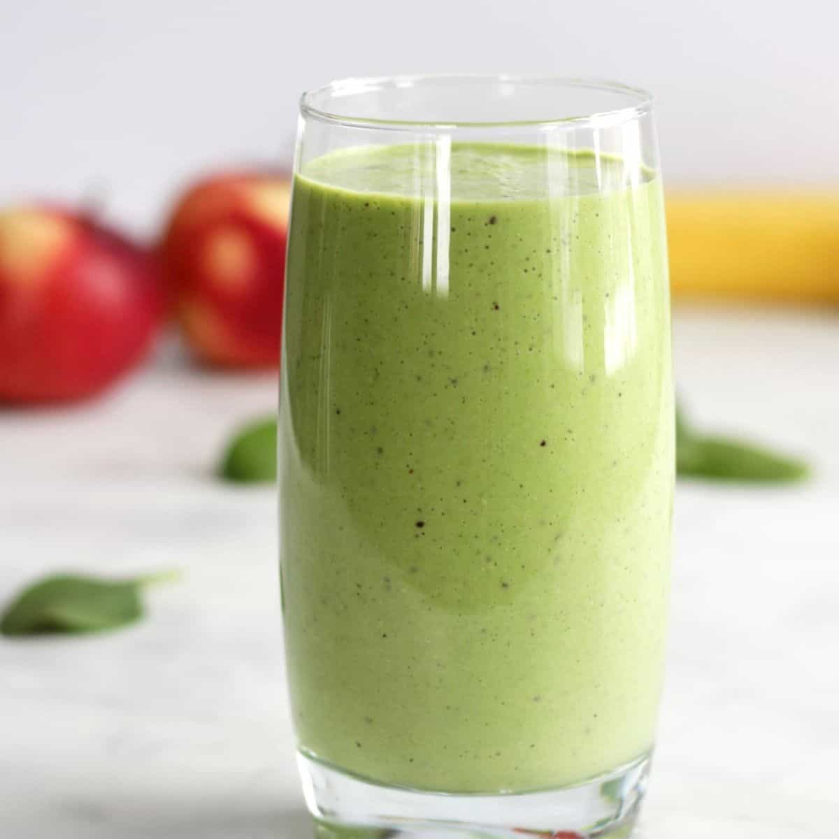 glass of green smoothie with apples and banana in background