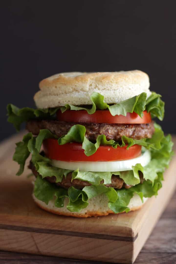 tall, stacked hamburger with tomato, onion, and lettuce in gluten free bun