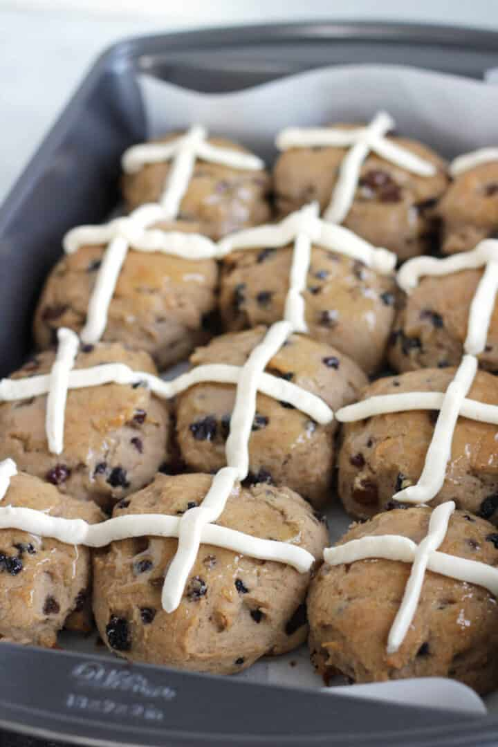 rows of gluten free hot cross buns with iced crossed on them sit in baking pan