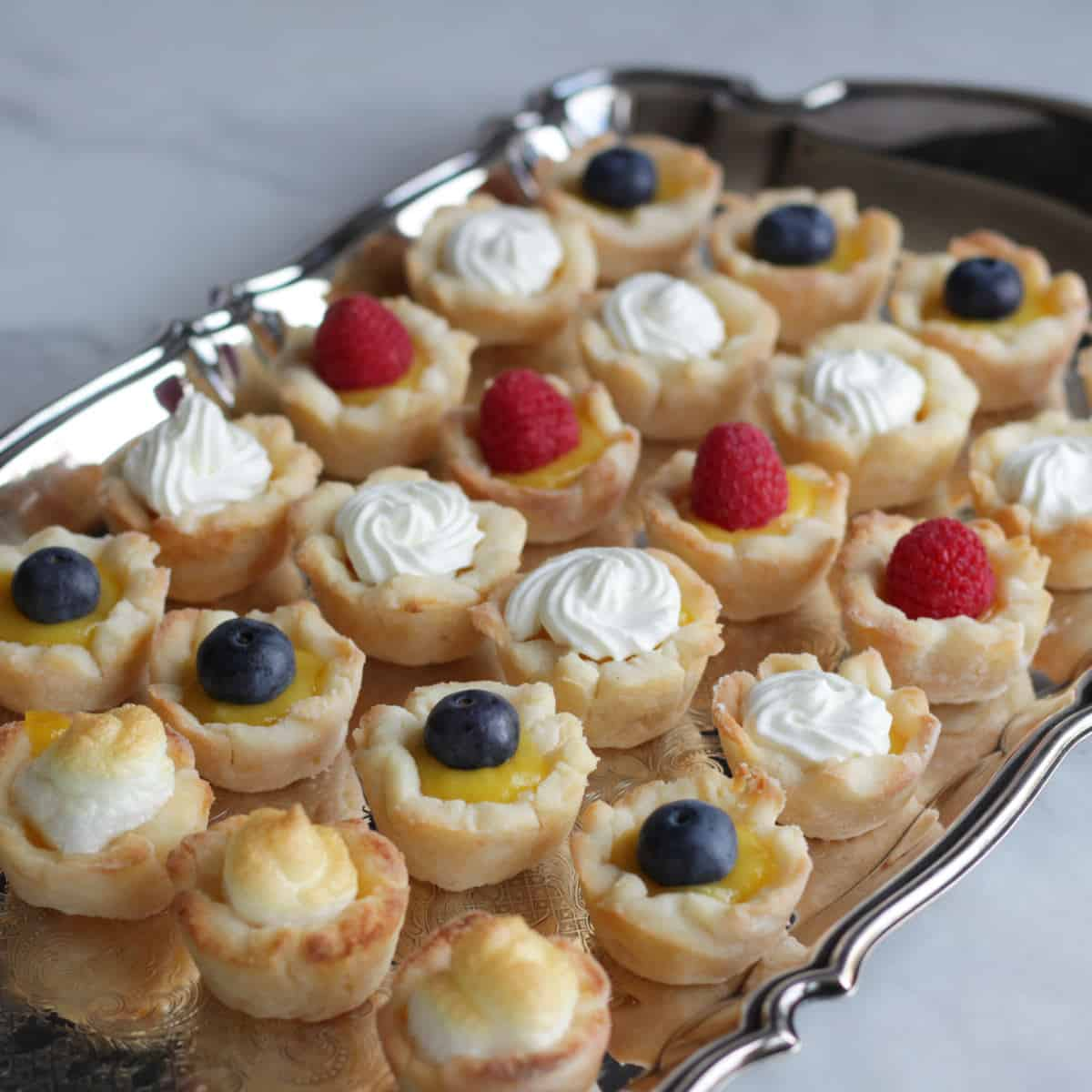 rows of mini lemon tarts garnished with berries, whipped cream, and meringue lined up in rows on silver tray