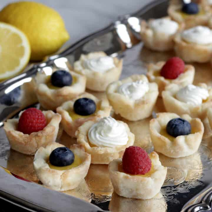 mini tarts topped with a berry or whipped cream scattered randomly on a silver platter