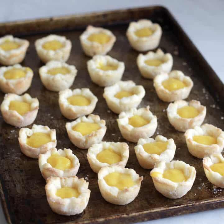24 mini tart shells filled with lemon curd, set in rows on baking sheet