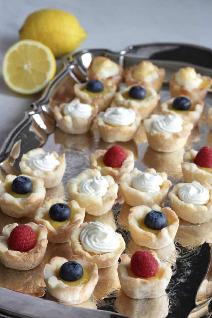 mini lemon tarts garnished with berries, whipped cream, and meringue sit on a silver tray with a couple fresh lemons in background