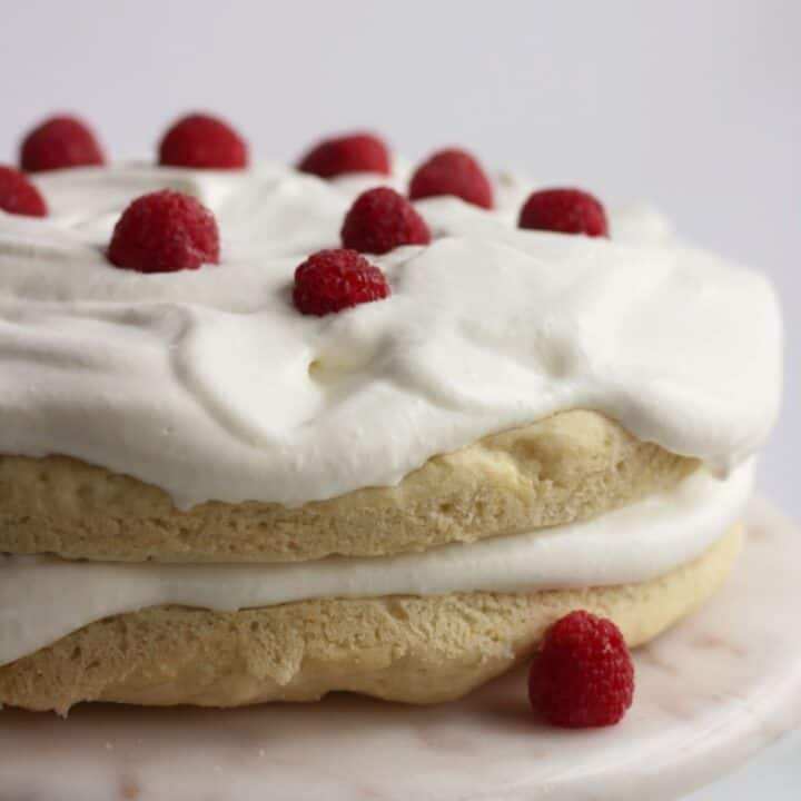 two round layers of gluten free vanilla cake topped with whipped cream and raspberries