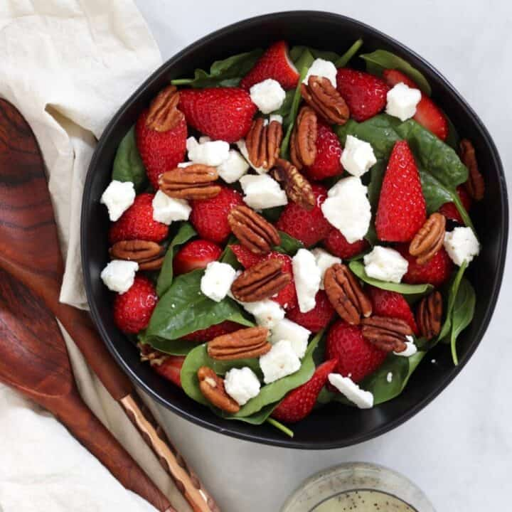 feta, pecans, strawberries, and spinach layered into a black bowl