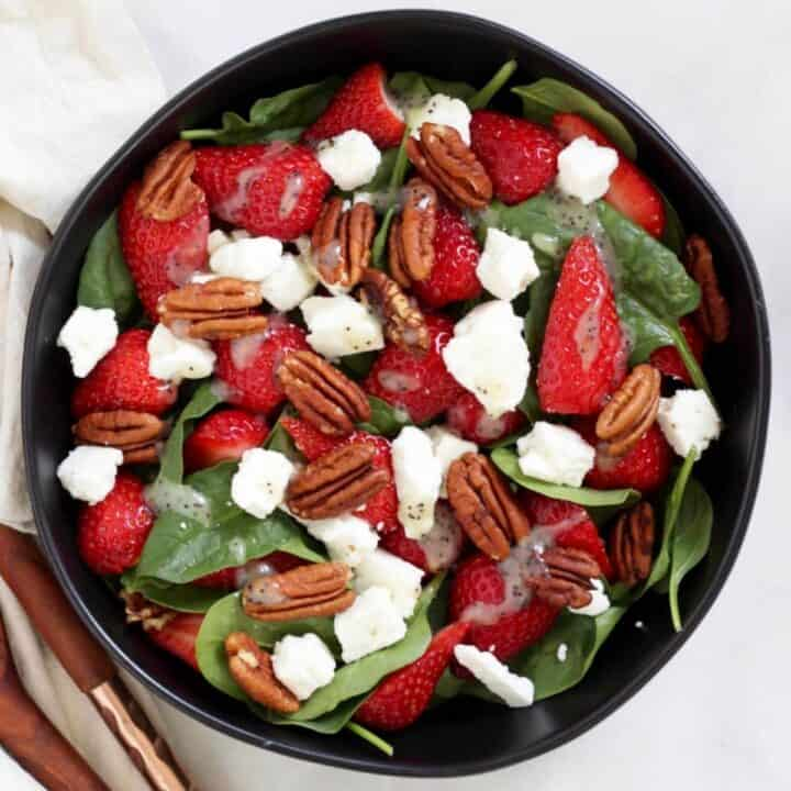 looking down on strawberry spinach salad with feta, poppy seed dressing, and pecans in black bowl