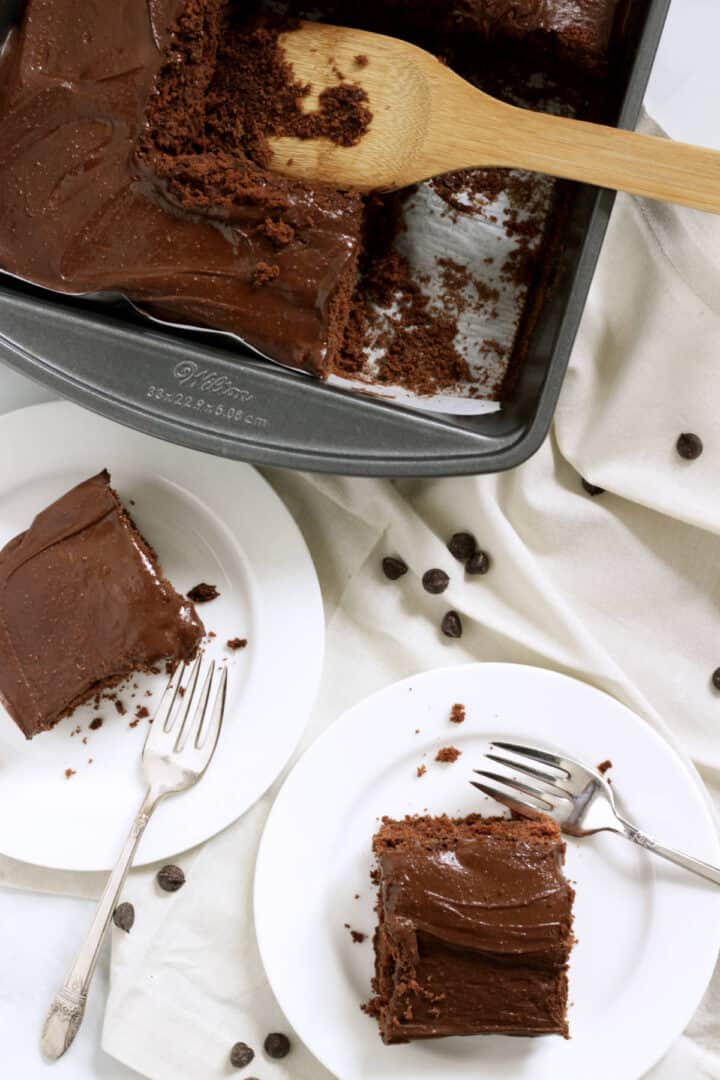 looking down on squares of frosted chocolate cake served on white plates from rectangular pan