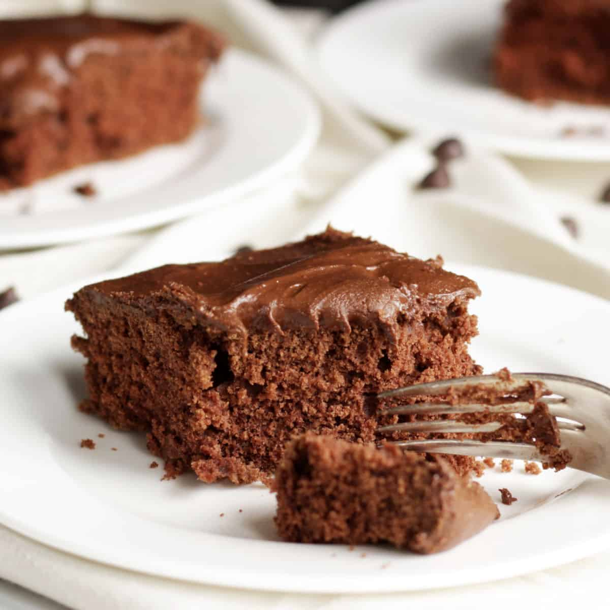 frosted chocolate cake on plate with fork breaking in