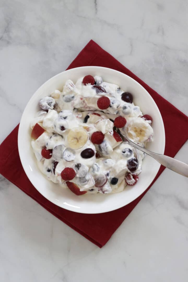 looking down into white bowl of fruit salad with whipped cream