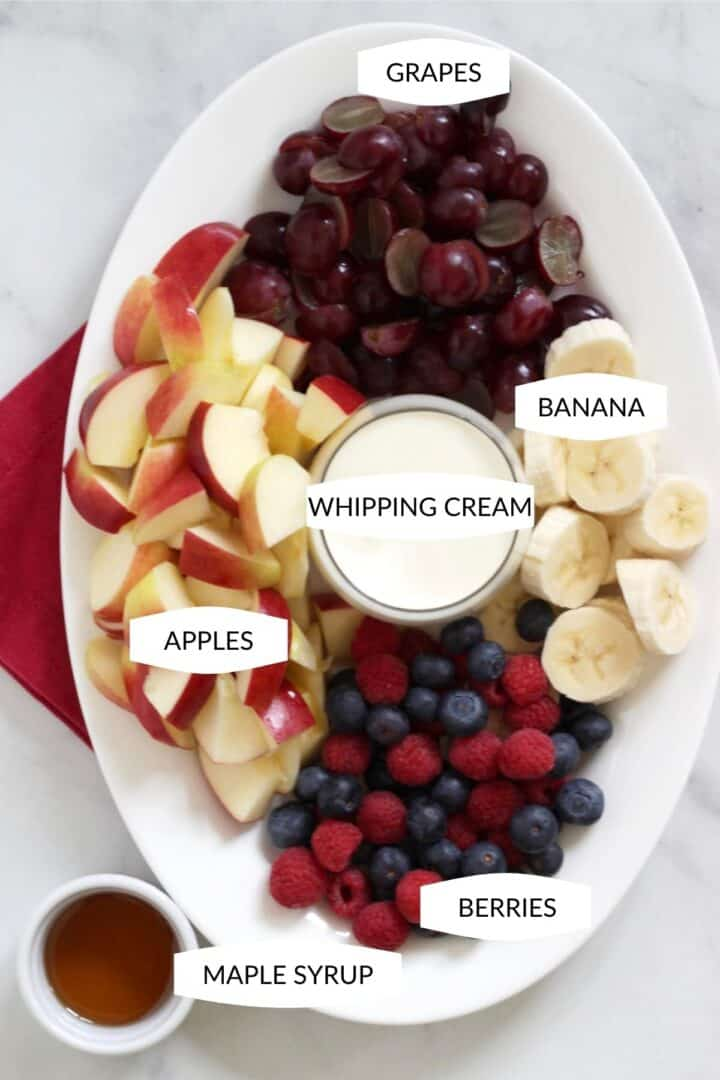 ingredients for fruit salad arranged in sections on a white oval platter