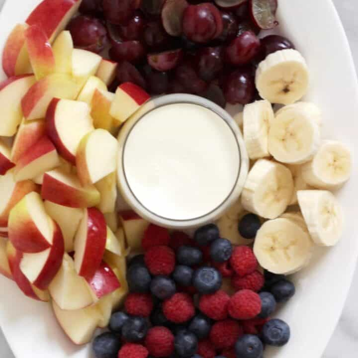 chopped apples, grapes, bananas, and whole berries arranged in sections on a white oval plate
