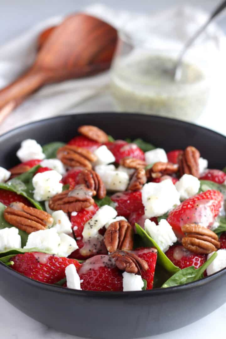 strawberry spinach salad in black bowl with poppy seed dressing in background