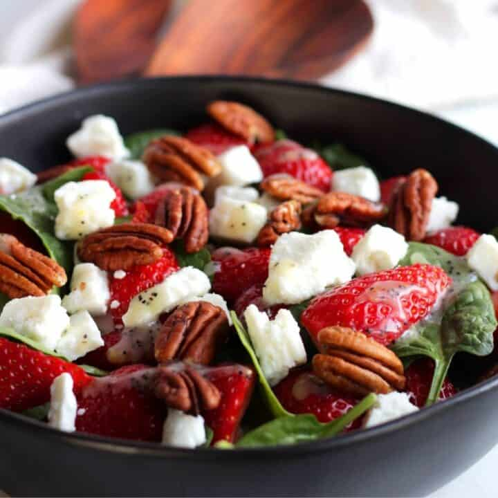 salad with strawberries, spinach, pecans, and feta cheese in black bowl