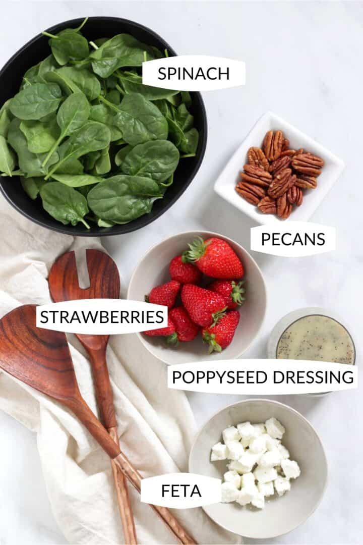 spinach, strawberries, pecans, feta cheese, and poppy seed dressing in small bowls with labels