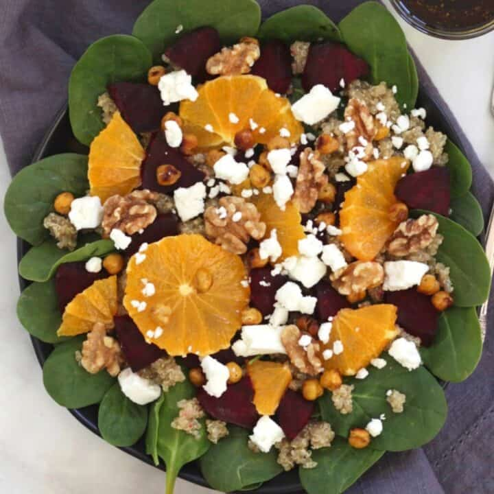 looking down on plate of orange segments, crumbled feta, chunks of roasted beets, and walnuts on fresh spinach - an assembled roast beetroot salad