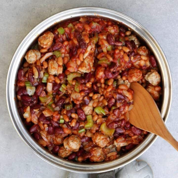looking down into a frying pan of bean cassoulet with a wooden spatula in it