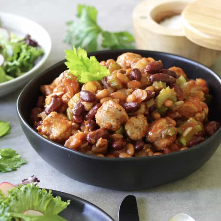 black bowl filled with sausage and bean cassoulet, garnished with leafy greens