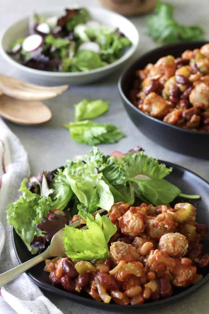 bean cassoulet and leafy green salad on two black plates