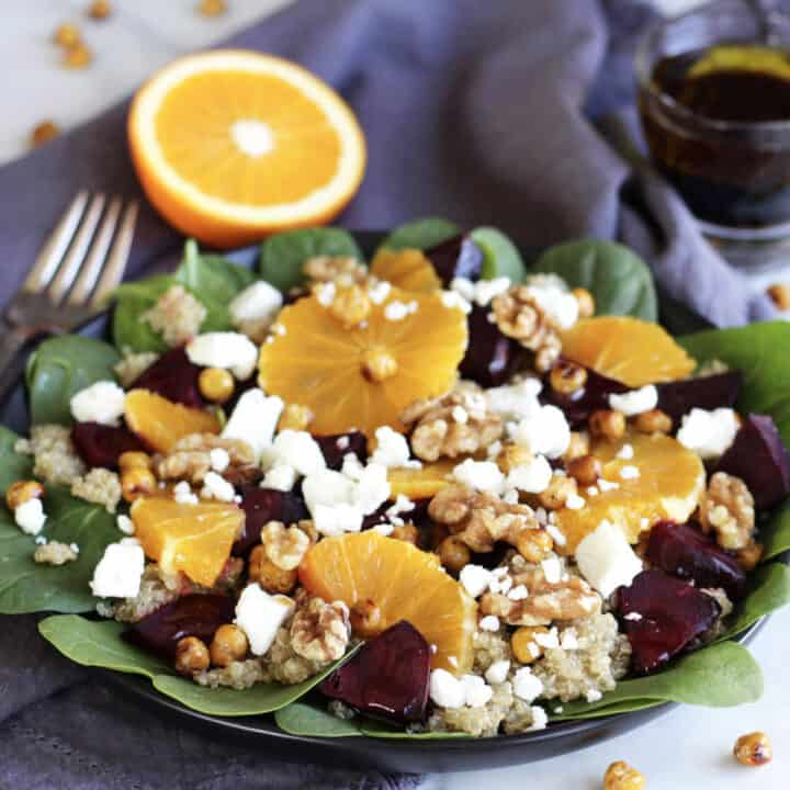 green salad topped with sliced beets, orange segments, feta cheese, and walnuts