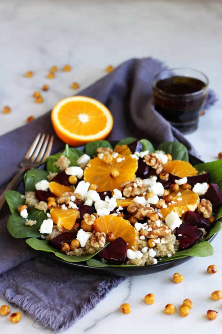 plated beet salad with orange segments, feta cheese, walnuts, and chickpeas on spinach