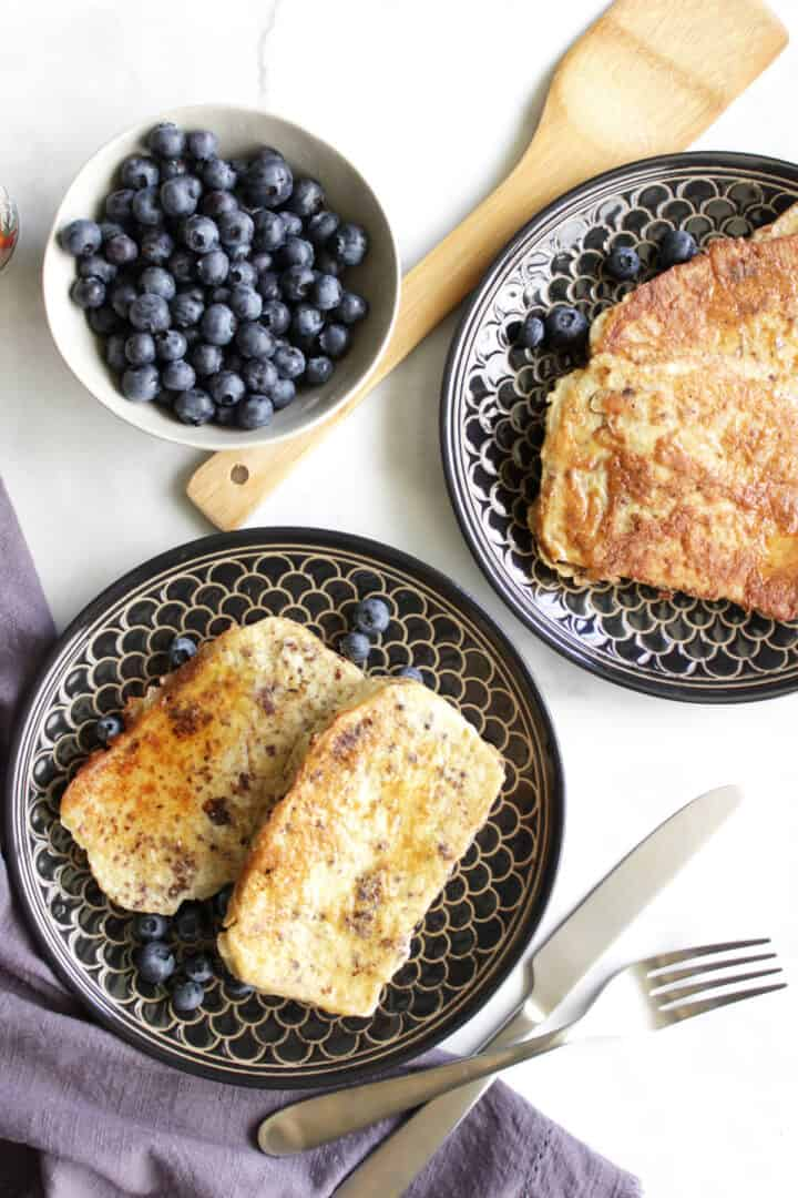 golden French toast on black plates by a bowl of blueberries, seen from above