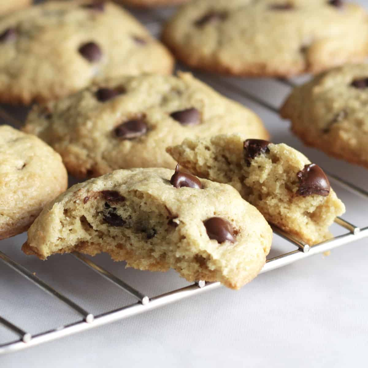 chocolate chip cookies cooling on a wire rack with one cookie broken open