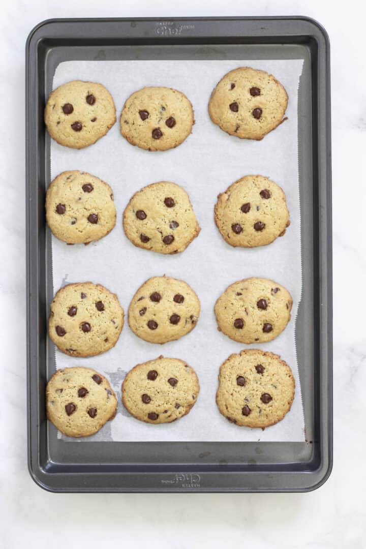 baked chocolate chip cookies on a parchment-lined baking sheet