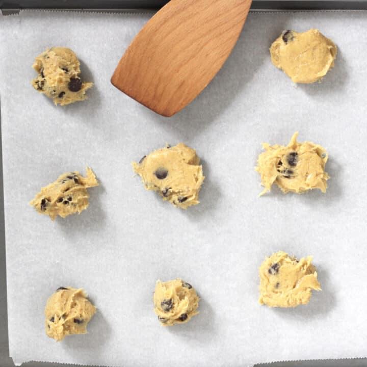 wooden spatula flattens the cookie dough balls a little