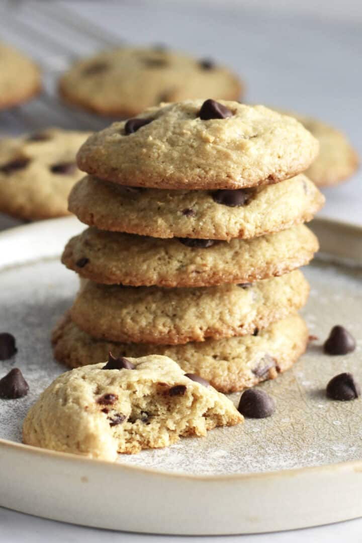 stack of chocolate chip cookies with a broken open cookie beside it
