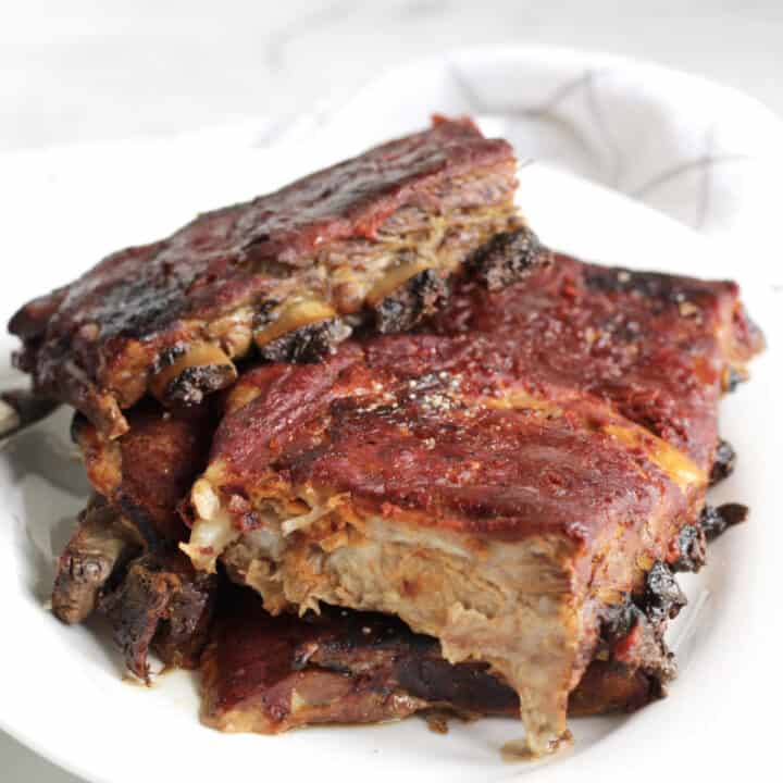 ribs in barbecue sauce piled on white plate
