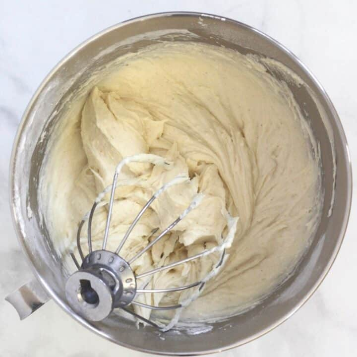 thick, white batter with stand mixer whisk attachment in bowl of stand mixer