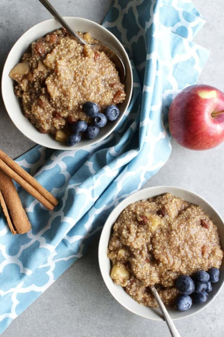 looking down on two bowls of quinoa porridge with blueberries, and blue napkin, apple, and cinnamon sticks around them