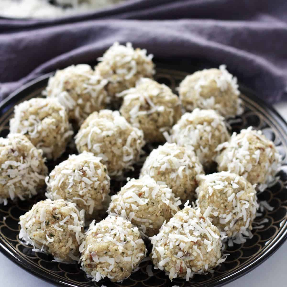 rows of golden balls coated in flaked coconut sitting on a black plate in front of lavender napkin