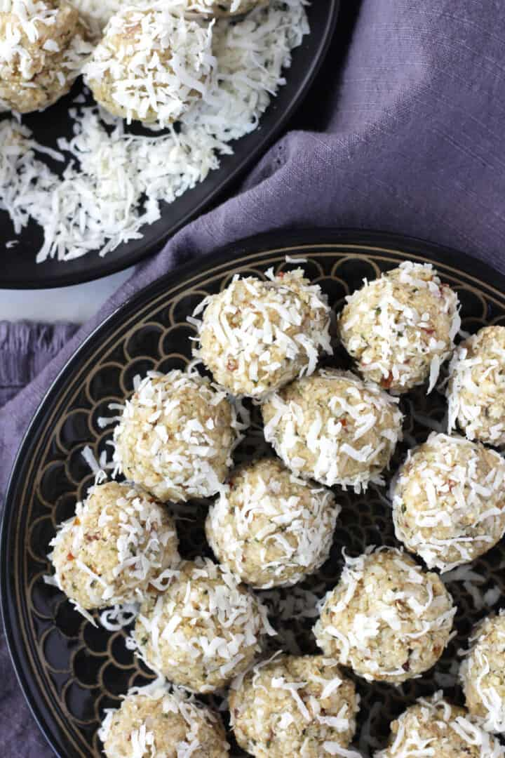 looking down on a round black plate filled with rows of coconut-coated protein balls