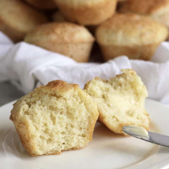 soft, fluffy, white dinner roll split open with butter on one half, more rolls in background