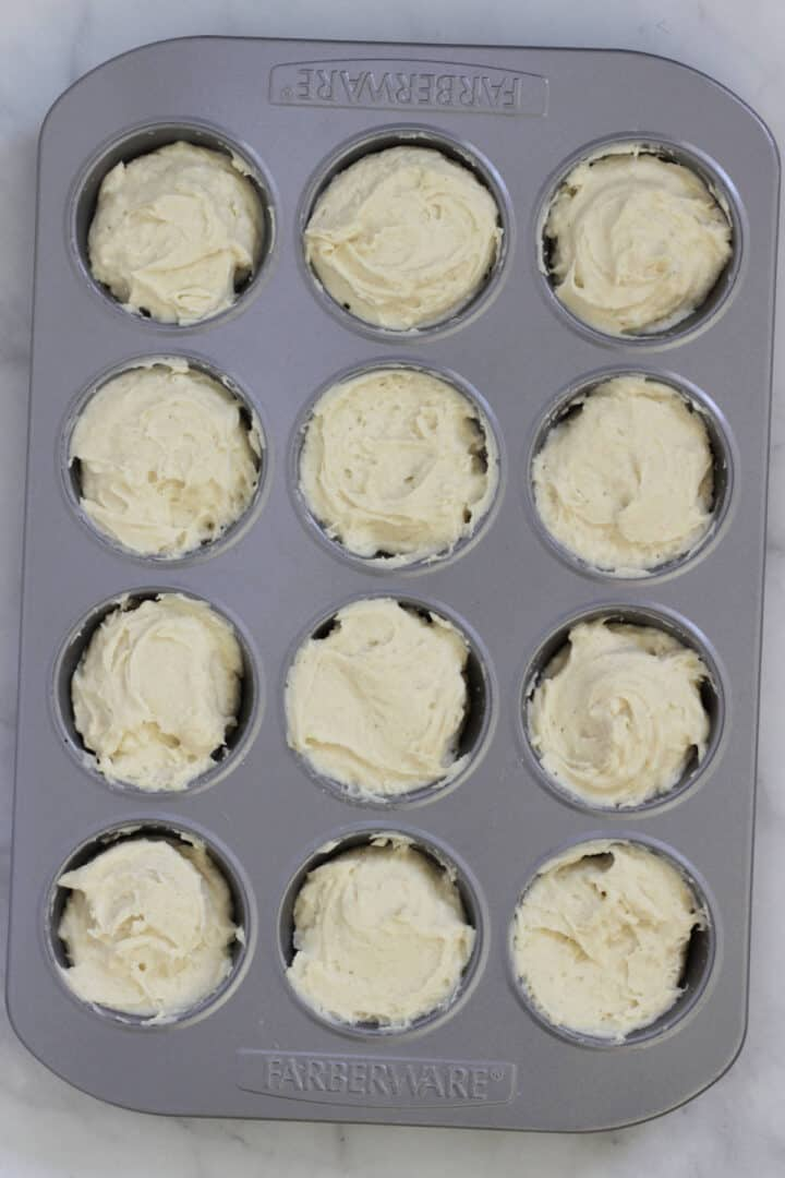 white batter in the 12 cups of a muffin pan