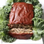 meatloaf topped with barbecue sauce, and one sliced lying down, resting in bed of kale