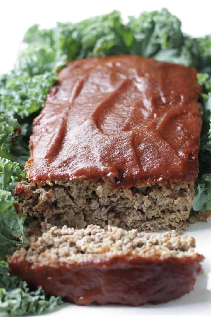 gluten free meatloaf with barbecue sauce on top and one end sliced off, surrounded by greens