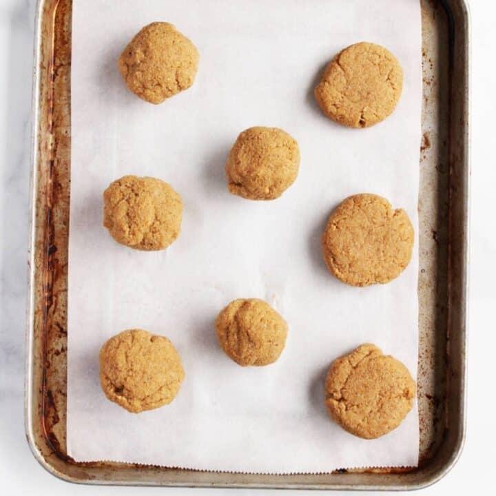 golden balls of dough on parchment-lined baking sheet