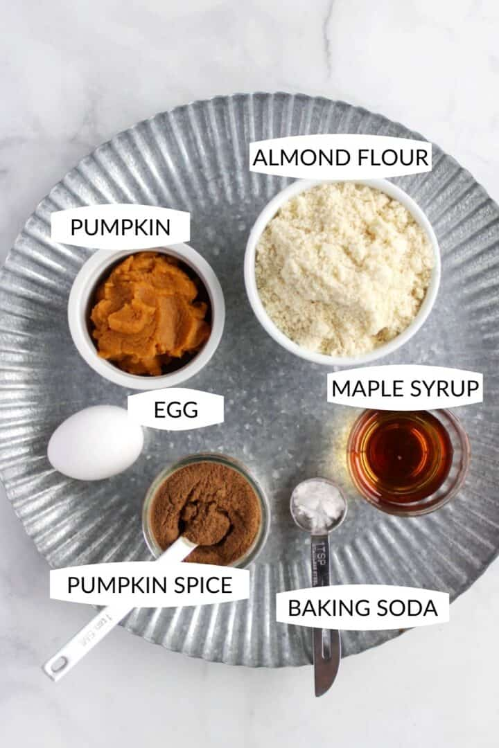 individual ingredients for pumpkin cookies in small bowls with labels