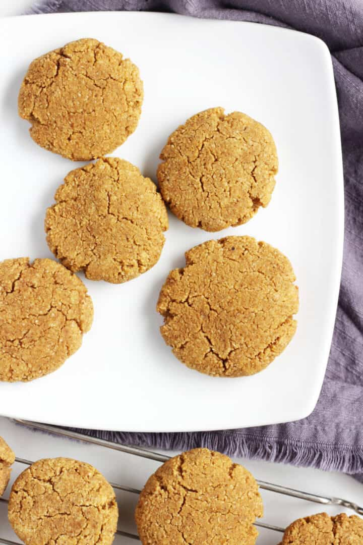 overhead view of golden pumpkin cookies on white plate over lavender napkin